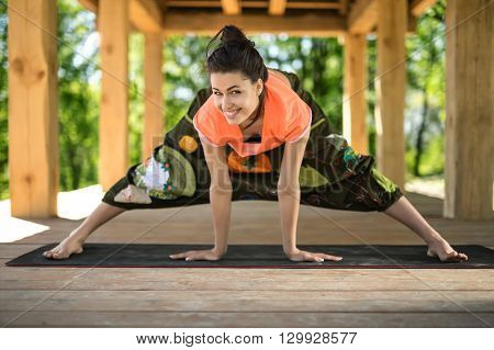 Handsome girl makes wide-legged forward bend on the black yoga mat on the wooden terrace on the nature background. She holds her hands on the mat. Her head is partially turned to the right and she looks into the camera with a smile. She wears orange t-shi