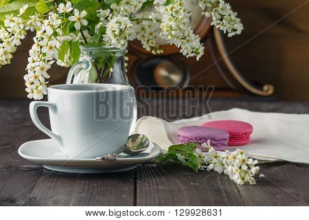 Kettle and cups with spring flowers on wood table