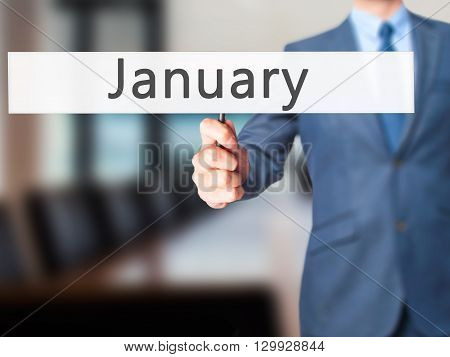 January - Businessman Hand Holding Sign