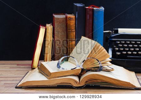Old books, glasses  and typewriter   - writting and publishing  concept
