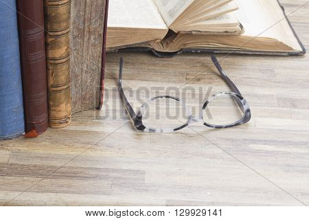 Books and glasses on wooden table background