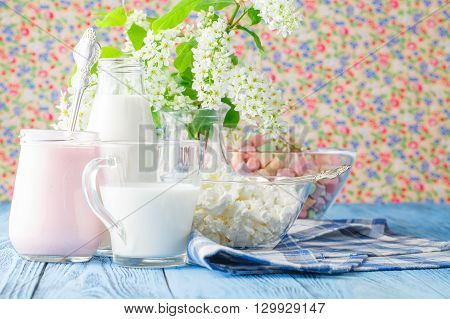 Colorful marshmallows in a glass jar on blue table