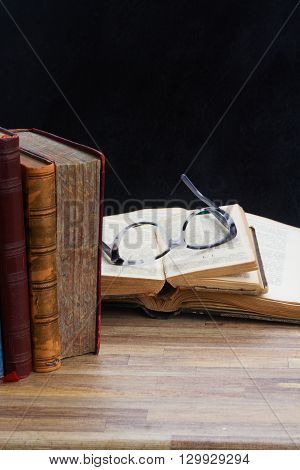 Open books and glasses on wooden table desktop, low key