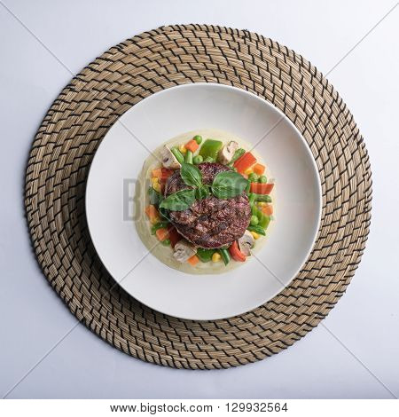 Thick cut beef filet steak served with mashed potatoes vegetables and mushroom on white porcelain dish