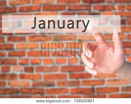 January - Hand Pressing A Button On Blurred Background Concept On Visual Screen.