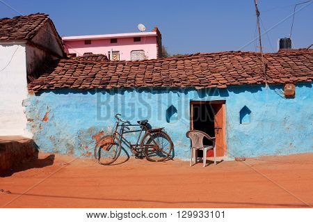 Bicycle and blue walled rural house in small indian town of Madhya Pradesh, India