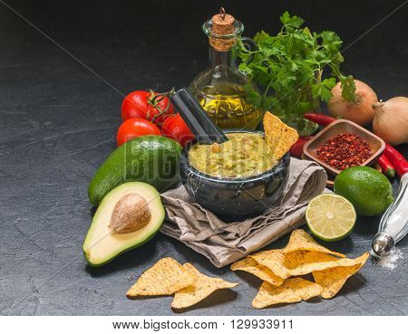 Bowl of delicious homemade Guacamole with nachos next to fresh ingredients on black background