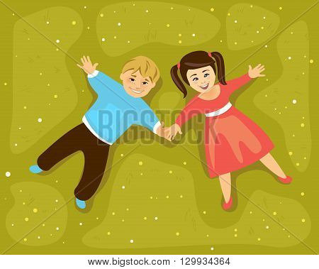 Boy and girl lying on a grass and holding hands