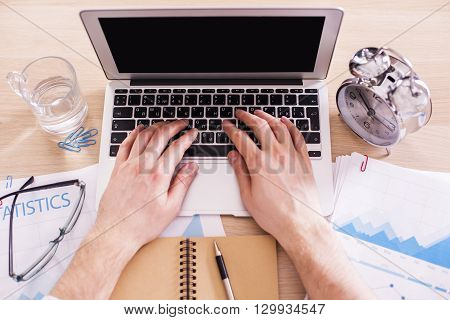 Topview of male hands typing on keyboard of laptop with blank screen on office desk with glass of water and alarm. Mock up