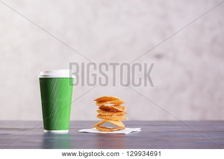 Closeup of wooden desktop with green take away coffee cup and pile of cookies on napkin. Blurry concrete background