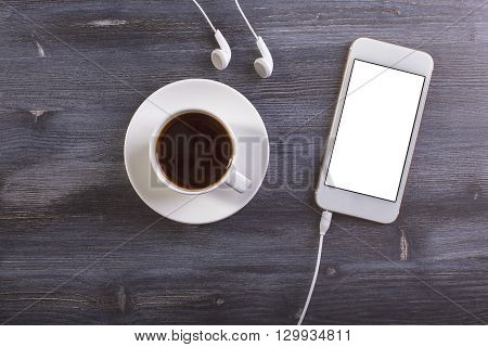 Topview of dark wooden desktop with coffee cup and saucer blank white phone and headphones. Mock up