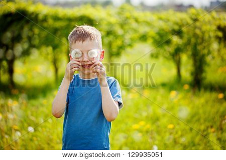Child with white blowing dandeion eyes on green background in a summer park. Concept happy childhood