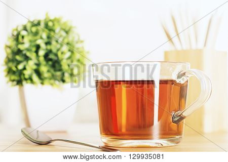 Wooden desktop with cup of tea teaspoon and small plant