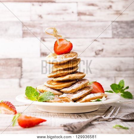 Stack of homemade dutch mini pancakes called poffertjes with strawberries and mint, sprinkled with powdered sugar. Healthy food concept with copy space.