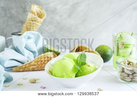 Homemade pistachio sorbet with lime, mint leaves, nuts and waffle cones. Selective focus