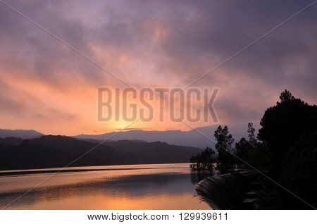 Beautiful landscape ofreservoir at sunset with colorful stormy sky reflections and mountains.