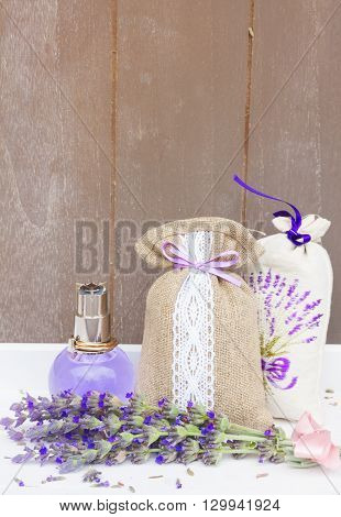 Lavender herbal  water, fresh flowers and dry in pouch, copy space on gray wooden planks
