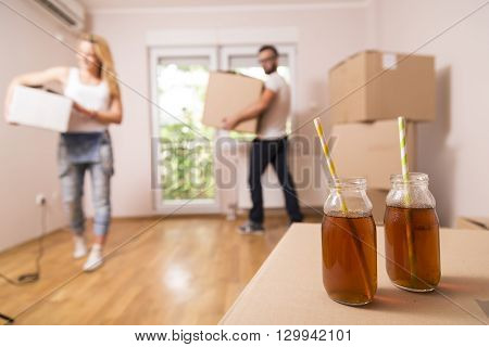 Young couple in love carrying cardboard boxes and moving in their new apartment. Two ice tea bottles with drinking straws placed on one of the cardboard boxes in focus