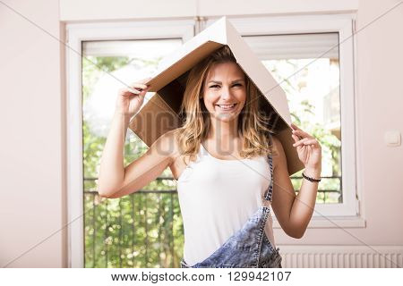 Young girl posing with a cardboard box on her head while unpacking things in her new apartment