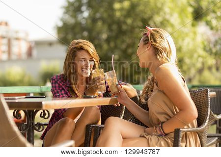 Beautiful attractive girls sitting in an outdoor cafe having an interesting conversation and drinking coffee