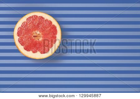 Popart style  red juicy grapefruit on a striped background top view. Striped background in blue and dark blue stripes. Red grapefruit located top left. Lines texture. Diagonal lines.