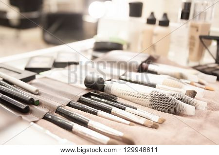 Makeup products and cosmetics on table in backstage in vintage style