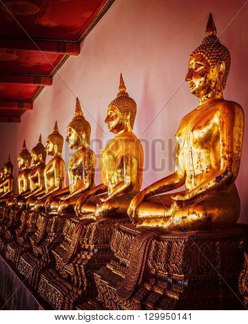 Travel Thailand Buddhism religion - vintage retro effect filtered hipster style image of row of sitting Buddha statues in Buddhist temple