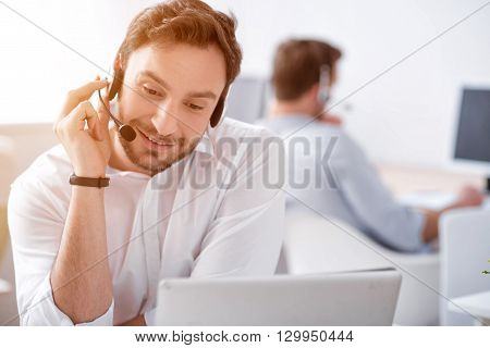 How can I help you. Cheerful content smiling man sitting at the table and using headset with micro while his colleague working in the background