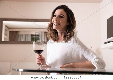 A beautiful young woman sitting at a glass table and enjoying a glass of wine.