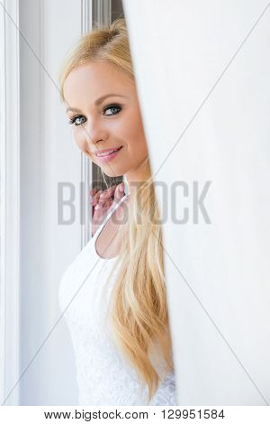 A beautiful young blond woman standing in the window