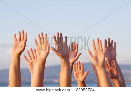 Group of people pulling hands in the air in sunlight