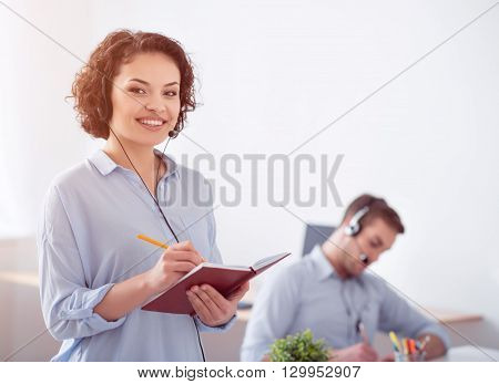 Nice professional. Cheerful delighted smiling woman making notes  and  using headset with micro while  her colleague working in the background