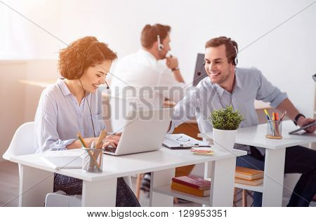 Lets have fun. Cheerful content smiling colleagues sitting at the table and working on the laptops while expressing gladness