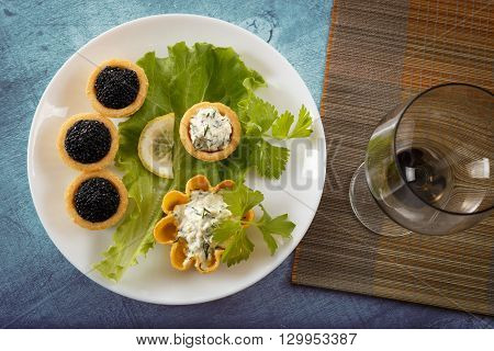 Tartlets filled with black caviar and cheese and dill salad on white plate and leaf against blue rustic wooden background with a wine glass on bamboo placemat horizontal top view