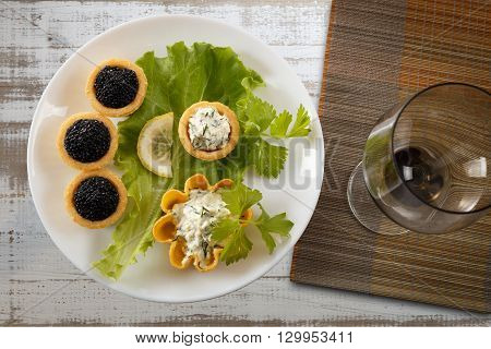 Tartlets filled with black caviar and cheese and dill salad on white plate and leaf against white rustic wooden background with a wine glass on bamboo placemat horizontal top view