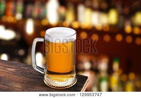 Mug of cold fresh beer on table, on dark pub background