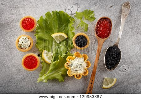 Tartlets filled with black caviar and cheese and dill salad on white plate and leaf against silver rustic wooden background with silver and wooden spoons full of caviar horizontal top view