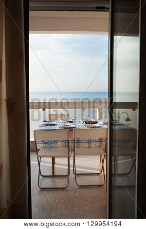 Dining table set on a balcony overlooking the sea viewed through an open door of the restaurant or apartment
