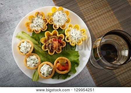 Tartlets filled with vegetables and cheese and dill salad on white plate and leaf against rustic wooden background with a wine glass on bamboo placemat horizontal top view