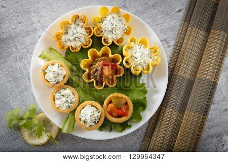 Tartlets filled with vegetables and cheese and dill salad on white plate and leaf against rustic wooden background with bamboo placemat horizontal top view