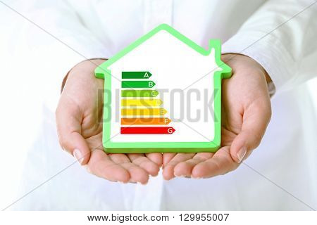 Female hands holding house with energy efficiency scale image