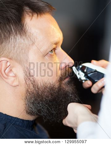 Man having his mustache and beard trimmed at a barber shop, close up side view of his head and the clippers or razor