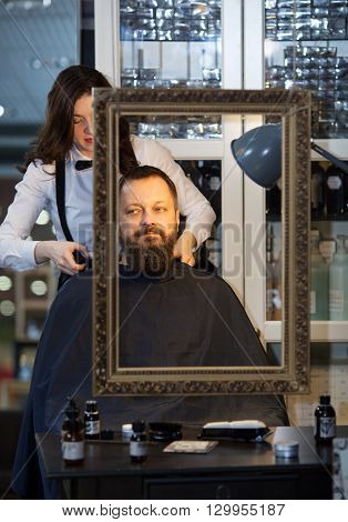 Middle-aged man having his beard and hair trimmed at an upmarket barber shop by a young woman in a bow-tie