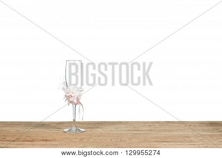 Wedding glass goblet decorated with artificial flowers stands on the old wooden table isolated on white background