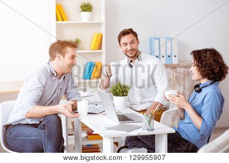 Have a little a break. Cheerful delighted smiling colleagues sitting at the table and drinking coffee while having a pleasant conversation