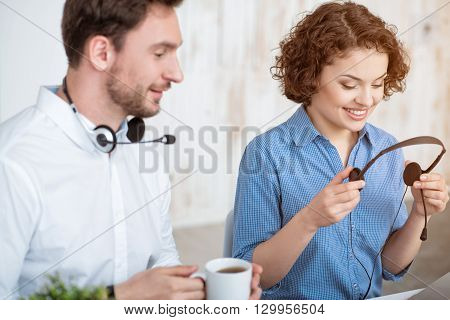Does it work. Pleasant cheerful beautiful woman holding headset with micro and sitting in the office while resting with her colleagues