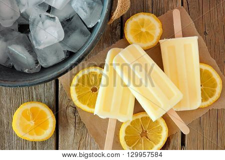 Homemade Lemon Yogurt Popsicles With Fresh Lemon Slices On Paper With Rustic Wood Background