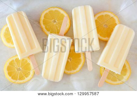 Healthy Lemon Yogurt Popsicles With Fresh Lemon Slices Scattered On A White Marble Background