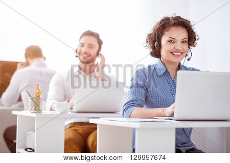 Charged with emotions Cheerful smiling beautiful woman sitting at the table and using headset with micro while her colleagues working in the background