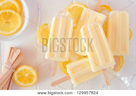 Lemon Yogurt Popsicles In A Transparent Serving Bowl Against A White Wood Background